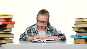 Girl chooses a book and starts to read it. White background stock footage
