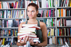 Girl chooses a book in university library. Brunete girl chooses a book in university library royalty free stock photography