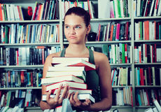 Girl chooses a book in university library stock photography