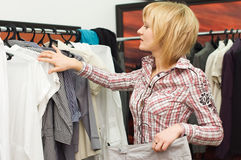 Girl chooses clothes in a boutique Stock Photography
