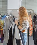 Girl chooses clothes in a boutique. Stock Photography