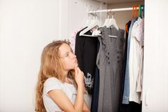 Girl chooses clothes from the closet. Child Stock Photos