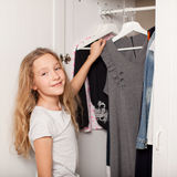 Girl chooses clothes from the closet. Child chooses clothes from the closet. Happy girl royalty free stock photography