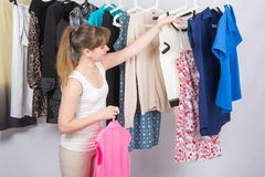 Girl chooses clothes Stock Images