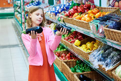 Girl chooses eggplants in supermarket Stock Images