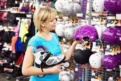 Girl chooses helmet for roller skating Royalty Free Stock Images