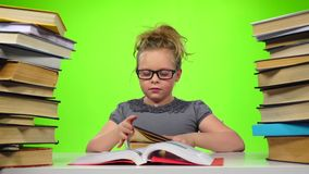 Girl chooses an interesting book and reads. Green screen. Slow motion stock footage