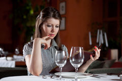 Girl chooses meal in restaurant Stock Photography