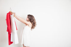 A girl chooses between red and white royalty free stock photo