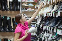 Girl chooses shoes at shoes shop Royalty Free Stock Photo