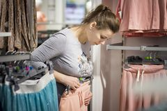 Girl chooses stylish clothes in modern boutique. woman buys new clothes stuff in the mall. young woman tries on her pants at shop. Shopping concept Royalty Free Stock Photo