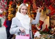Girl chooses to holiday decor Royalty Free Stock Photos