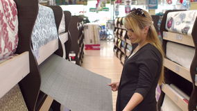 Girl chooses wallpaper in the building store stock video
