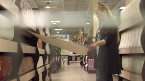 Girl chooses wallpaper in the building store. Woman selects wall-paper on the shelves in the store stock video