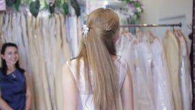 Girl chooses a wedding dress in a wedding salon stock video