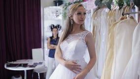 Girl chooses a wedding dress in a wedding salon stock video footage