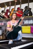 Girl choosing acoustic guitar Stock Images