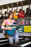 Girl choosing acoustic guitar Royalty Free Stock Photography