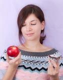 Girl choosing an apple. Pretty girl on a diet choosing between an apple and a cupcake Stock Image