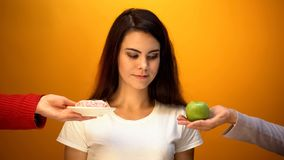 Girl choosing apple instead of donut, natural sugar and vitamin vs confectionery stock photography