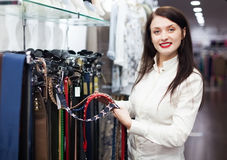 Girl choosing belt at shop Royalty Free Stock Photo