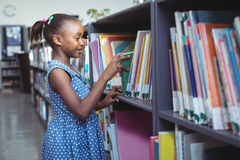 Girl choosing book in library. Girl choosing book from bookshelf in library Royalty Free Stock Images