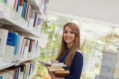 Girl choosing book in library and smiling Stock Photo