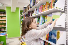 Girl choosing books in bookstore. First grader choosing books in bookstore for school royalty free stock photography