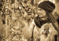 Girl choosing Christmas decoration at market Stock Images