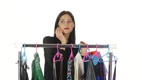 Girl choosing clothes in a department store and talking on the phone. White stock footage