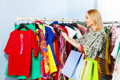 Girl choosing clothes hanging in a row Stock Image