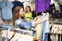 Girl choosing cloths in shop Royalty Free Stock Photos