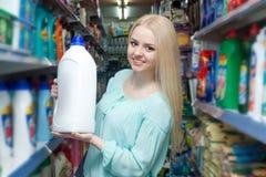 Girl choosing detergent Royalty Free Stock Image