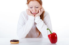 Girl choosing between doughnut and red peppers Royalty Free Stock Image