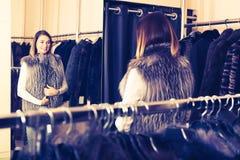 Girl choosing fur vest Stock Image