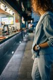 Girl choosing meal in street cafe, looking at glowing shop windo. W. Candid portrait of young woman standing at night near fast food restaurant, city lights royalty free stock images