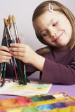 Girl choosing a paint brush. Happy young smiling girl selecting a brush to paint her picture royalty free stock photo