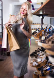 Girl choosing pair of shoes in store Royalty Free Stock Photo