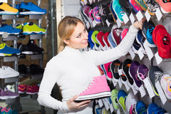 Girl choosing a pair of trainers in the store Royalty Free Stock Images