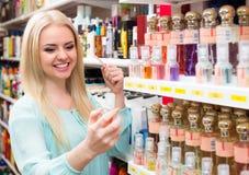 Girl choosing perfume in shop Stock Photography