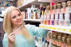 Girl choosing perfume in shop Royalty Free Stock Photography