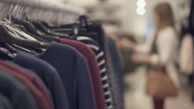 Girl choosing pullover clothes, blurred backgound. Selective focus Stock Image