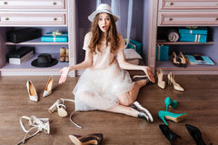 Girl choosing shoes in her wardrobe. Young pensive beautiful girl choosing shoes in her wardrobe Stock Photos