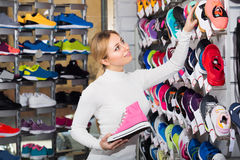 Girl choosing shoes in store Royalty Free Stock Images