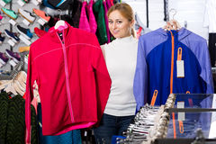 Girl choosing a sporty jacket Royalty Free Stock Image