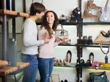 Girl choosing summer women shoes. Girl with a guy choosing summer women shoes in a shoe store royalty free stock photo