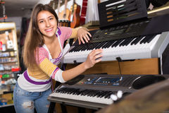 Girl choosing synthesizer in store Royalty Free Stock Photos
