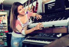 Girl choosing synthesizer in store Royalty Free Stock Images