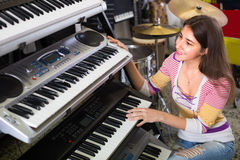 Girl choosing synthesizer in store Stock Images