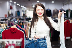Girl choosing trousers at boutique Royalty Free Stock Image
